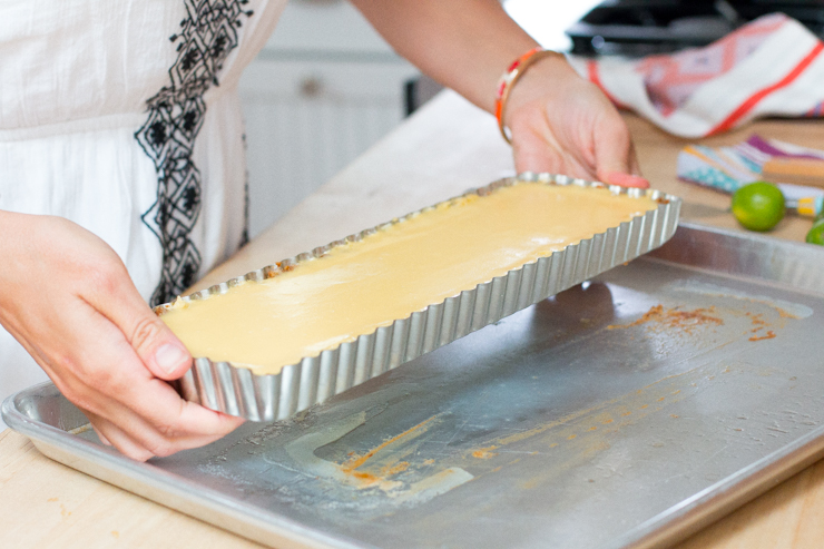 Carefully pop the key lime tequila tart out of the pan by pushing the removable bottom up.