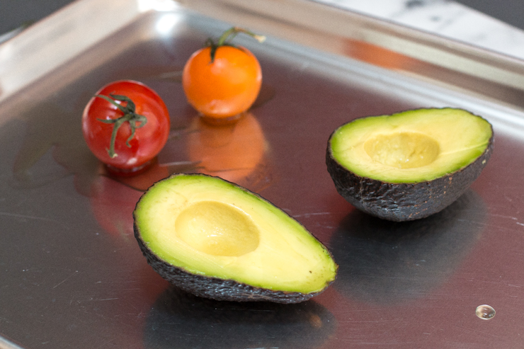 avocado and tomato on a baking sheet