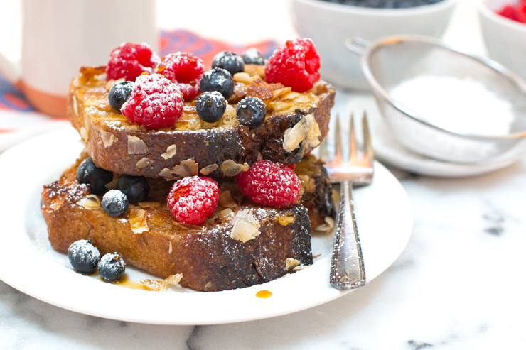Coconut French Toast stacked with fresh berries and coconut nectar, stacked two high