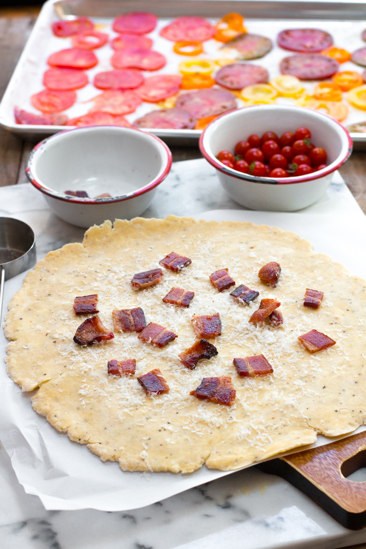 BLT Galette assembly. Bacon chopped up and sprinkled on the dough with grated pecorino cheese