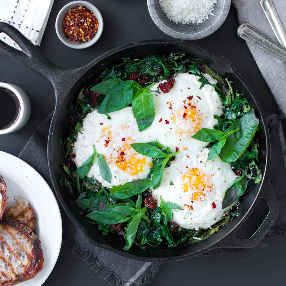 Baked Eggs with Ricotta, Greens & Sun Dried Tomatoes