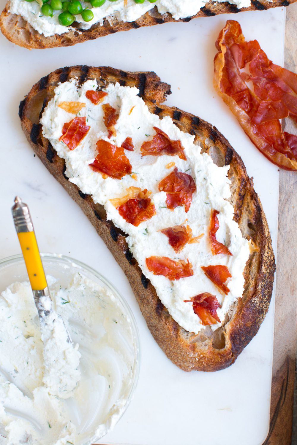 grilled Gjusta sourdough with goat cheese spread and crispy prosciutto
