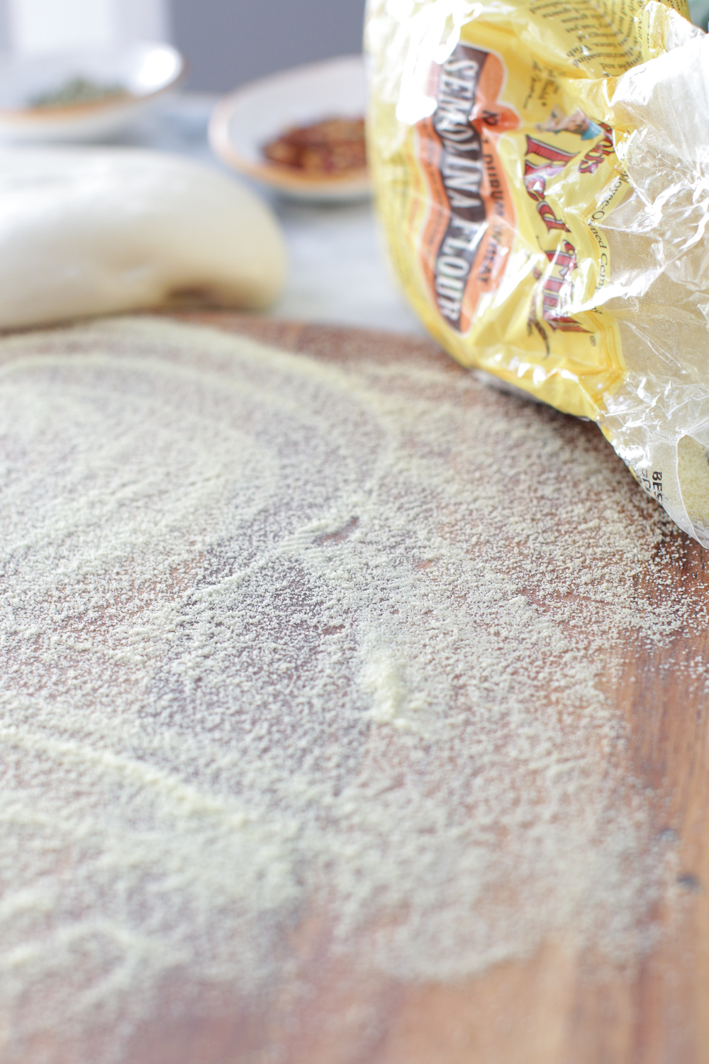 A sprinkle of Semolina Flour from Bob's Red Mill will keep the pizza dough from sticking to the peel by working like a set of ball bearings when transferring the dough to the steel.