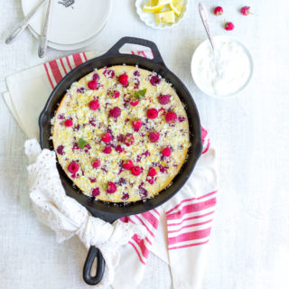 Raspberry Buttermilk Clafoutis topped with fresh raspberries and lemon sugar served with rich crème fraîche.