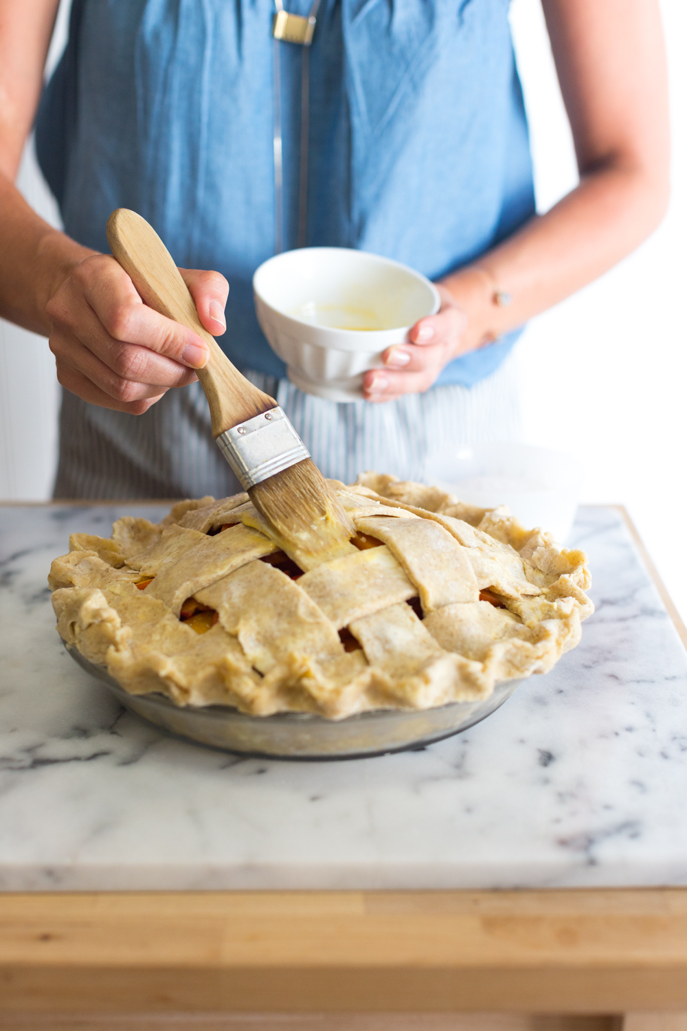 A baker brushing a peach pie with an egg wash.