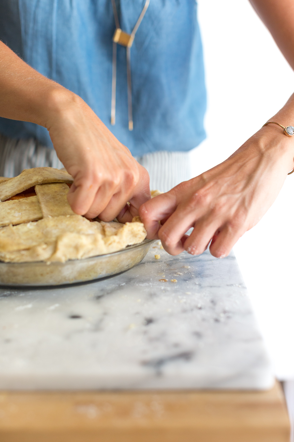 A baker shows how to flute the edge of a pie crust.