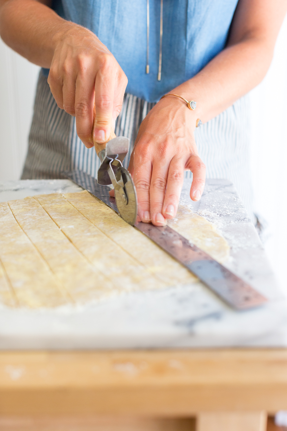 "Use a metal ruler and a pizza cutter to slice 1"" wide dough strips for weaving the top of the peach pie crust."