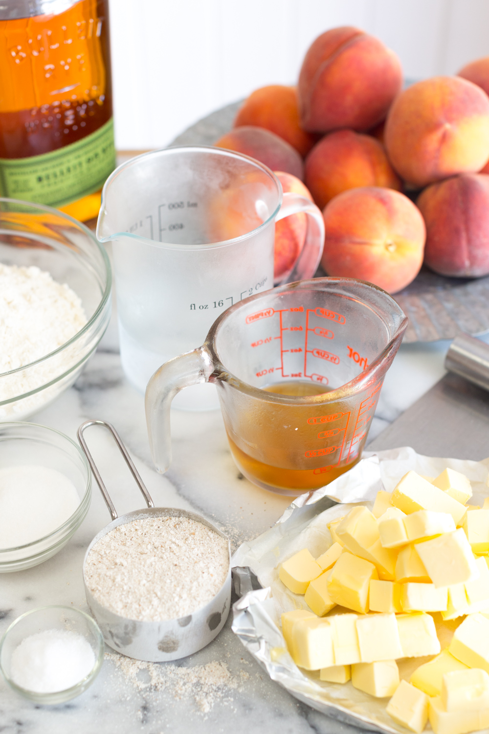 Ice cold ingredients for rye flour pie dough. Butter, rye whiskey, rye flour, peaches.