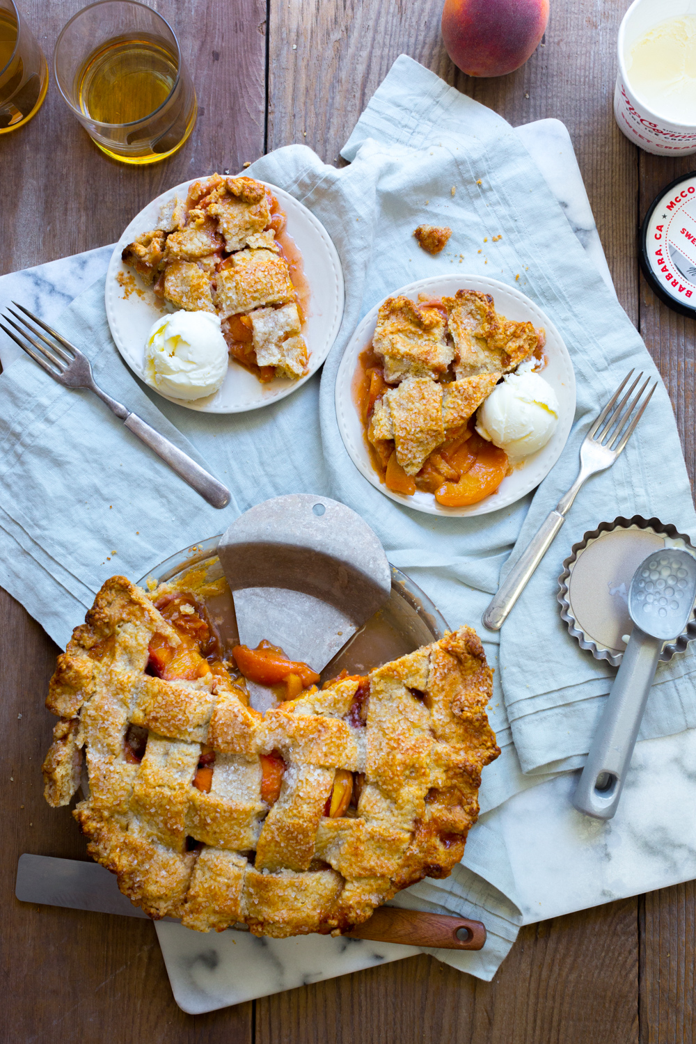 Creamy cold scoops of ice cream on thick, juicy slices of Rye Rye Peach Pie.
