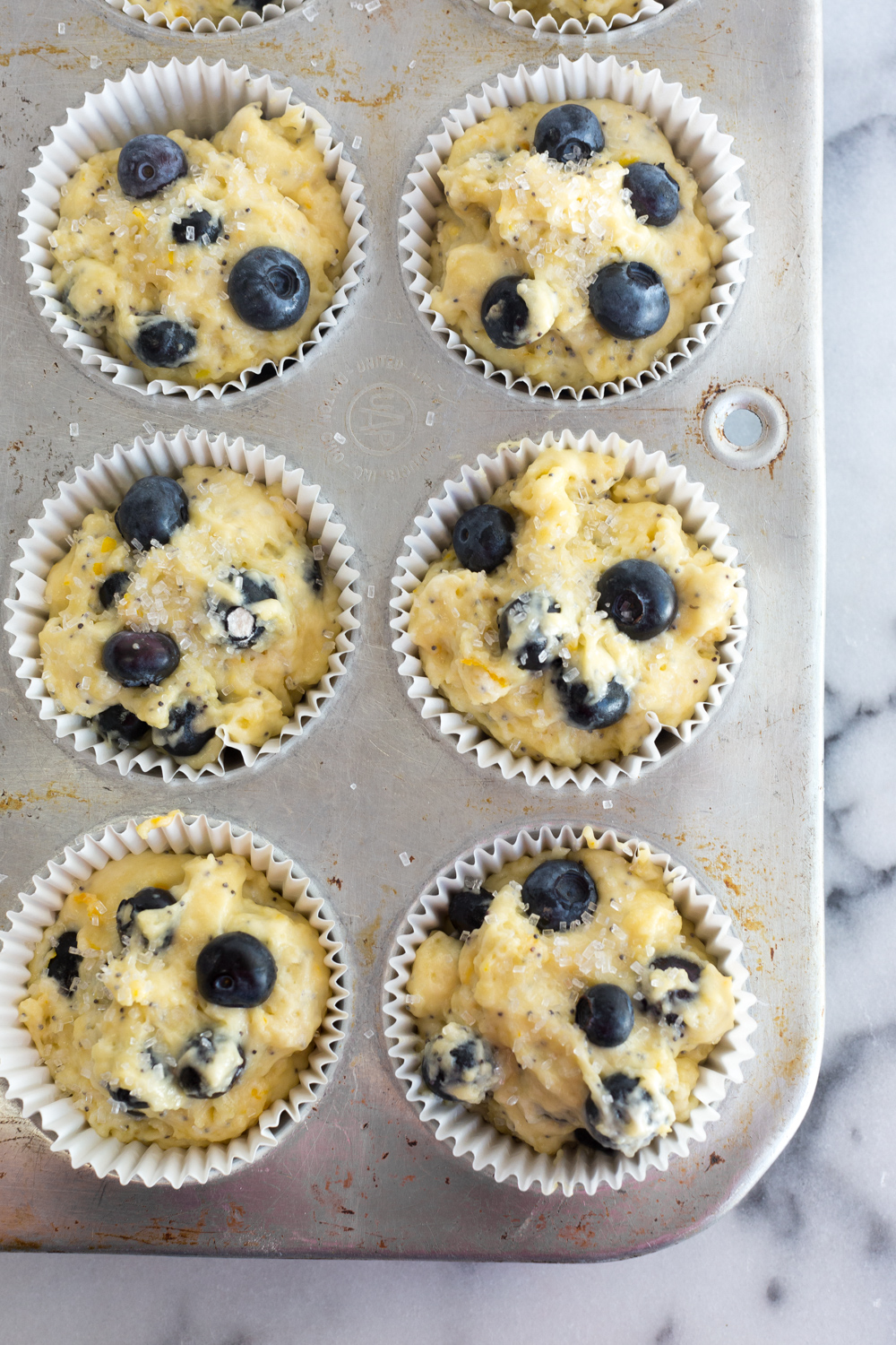 Muffin tin filled with Blueberry Lemon Poppy Seed Muffin batter.